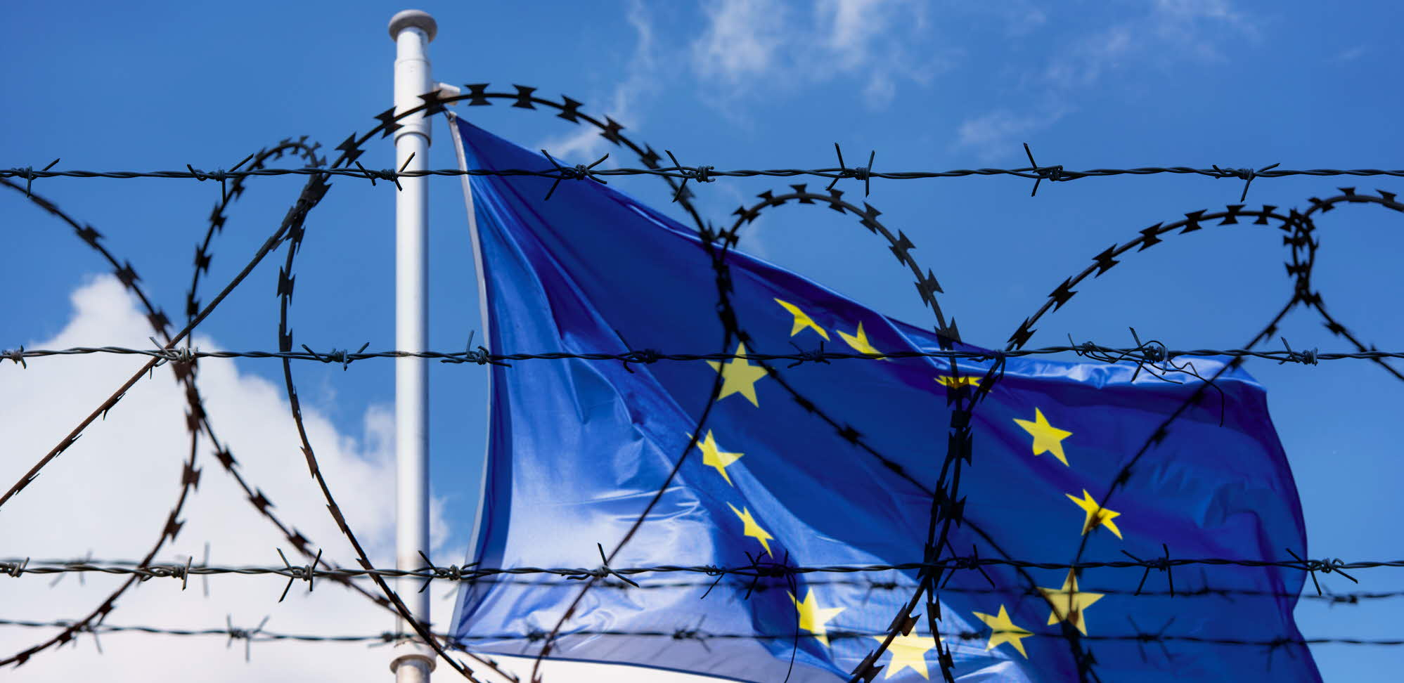 EU flag behind barbed wire