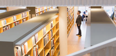 Student looking at a book shelf, searching for books at Linnaeus University Library