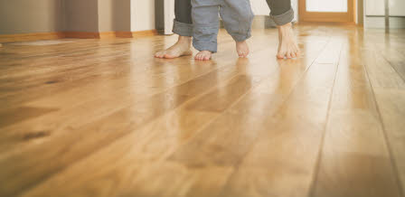 dad's and child's bare feet on a wooden floor