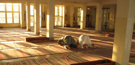 Two people praying in a Mosque