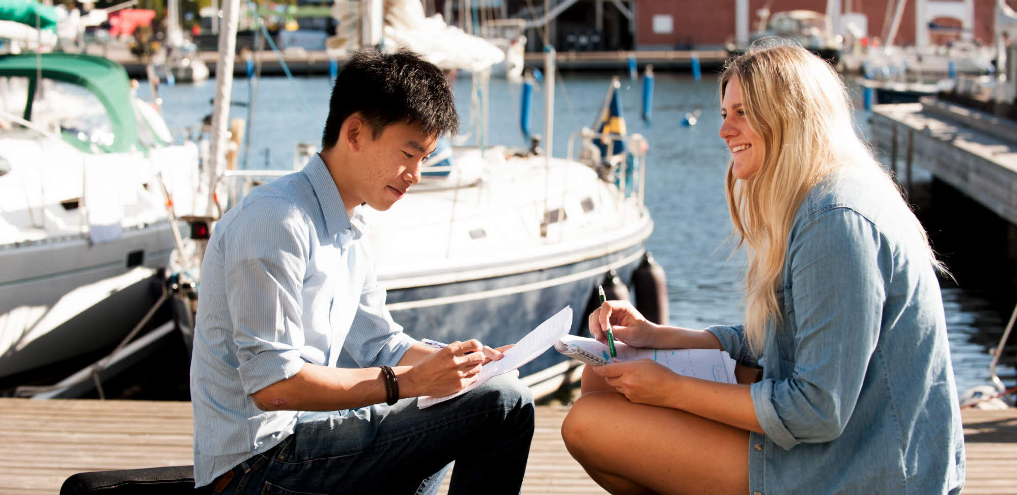 Two summer academy students sitting on a pier.