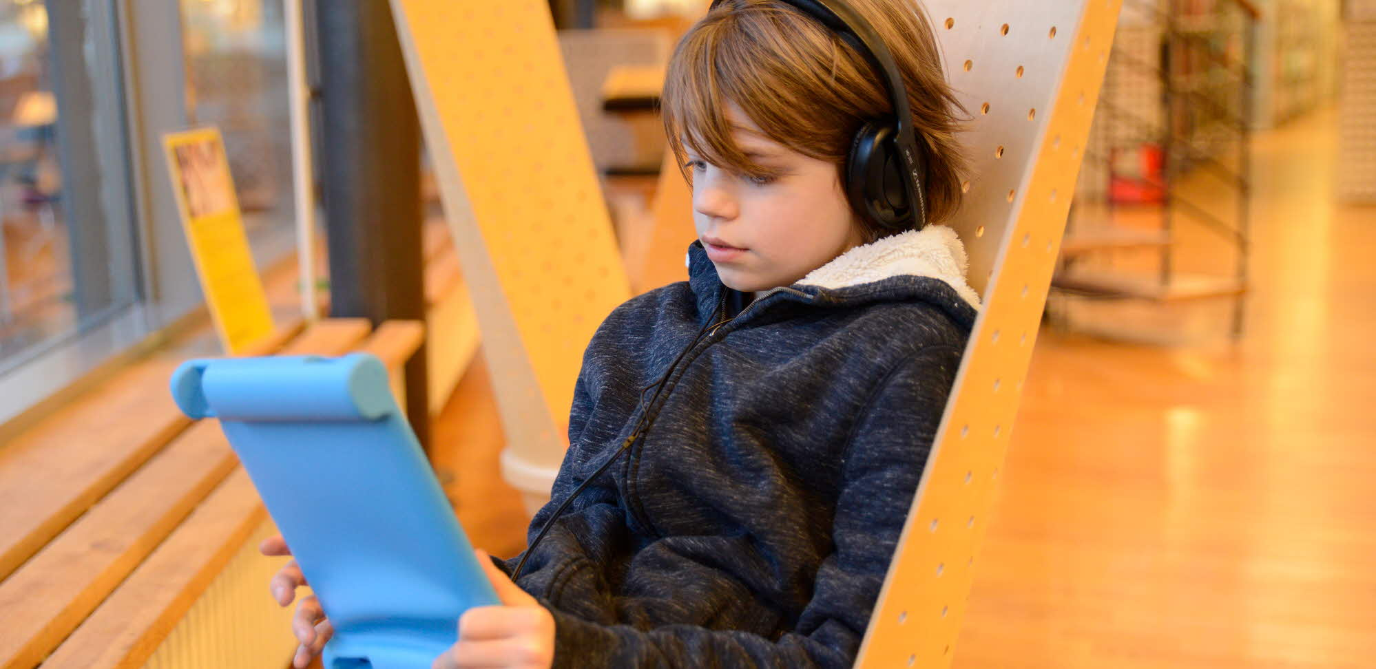 Child listening and reading on a tablet